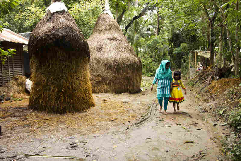 Minu walks with her 7-year-old daughter, Sumaiya, in her home village outside Chittagong, Bangladesh. Minu and her sister Shumi are both garment workers and are able to send money home to support their parents.