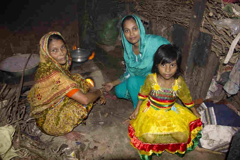 Minu's mother, Noor Jahan Begum (left), sits near the family stove with Minu and Sumaiya. Sumaiya lives here with Minu's parents.