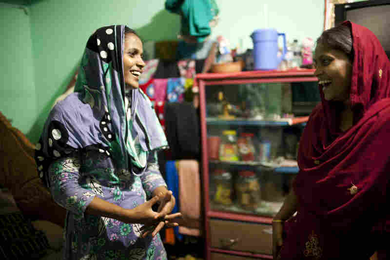 Shumi (left) and Minu inside the small room they share with Minu's husband in Chittagong.