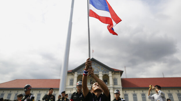 An anti-government protester waves a national flag after breaking into the compound of the Royal Thai Army headquarters in Bangkok on Friday.