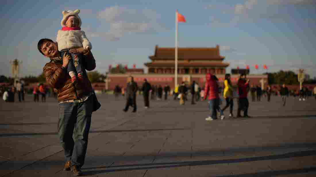 A man and child walk in Beijing's Tiananmen Square. China's government recently announced an easing of the country's one-child policy. While the move appears to be broadly supported, many urban Chinese parents say it would be hard to afford a second child.