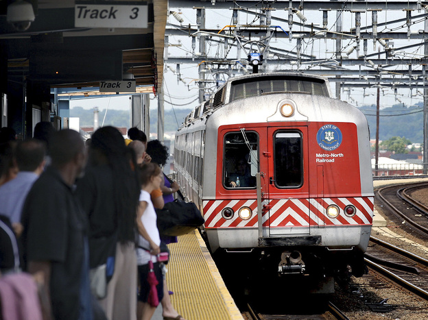 Commuters wait on the platform as a Metro-North train arrives in Bridgeport, Conn.