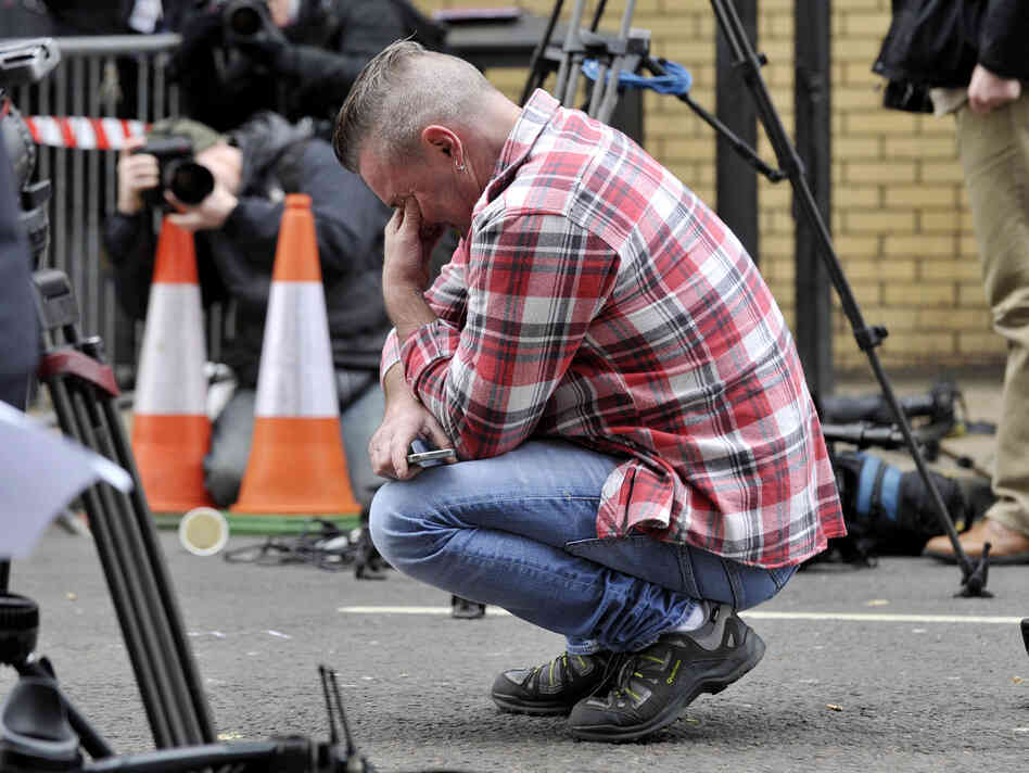 Glasgow resident Paul Watt, 48, crouches near a police cordon in Glasgow on Saturday. Watt was a regular patron of the pub hit by an out-of-control police helicopter.