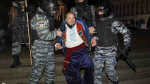 Ukrainian riot police officers detain an activist during a rally demanding the resignation of President Viktor Yanukovych.