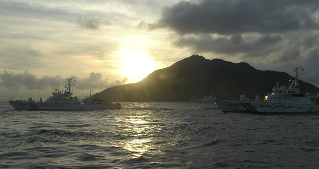 Japanese Coast Guard vessels sail alongside Japanese activists' fishing boat, not in photo, warning the activists away from a group of disputed islands called Diaoyu by China and Senkaku by Japan.