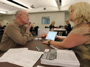 Health care specialist Stacy Chagolla helps William Bishop compare plans at an Af