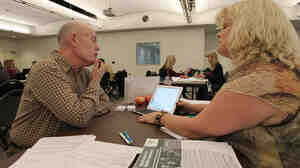Health care specialist Stacy Chagolla helps William Bishop compare plans at an Affordable Care Act enrollment fair in Pasadena, Calif., this month.