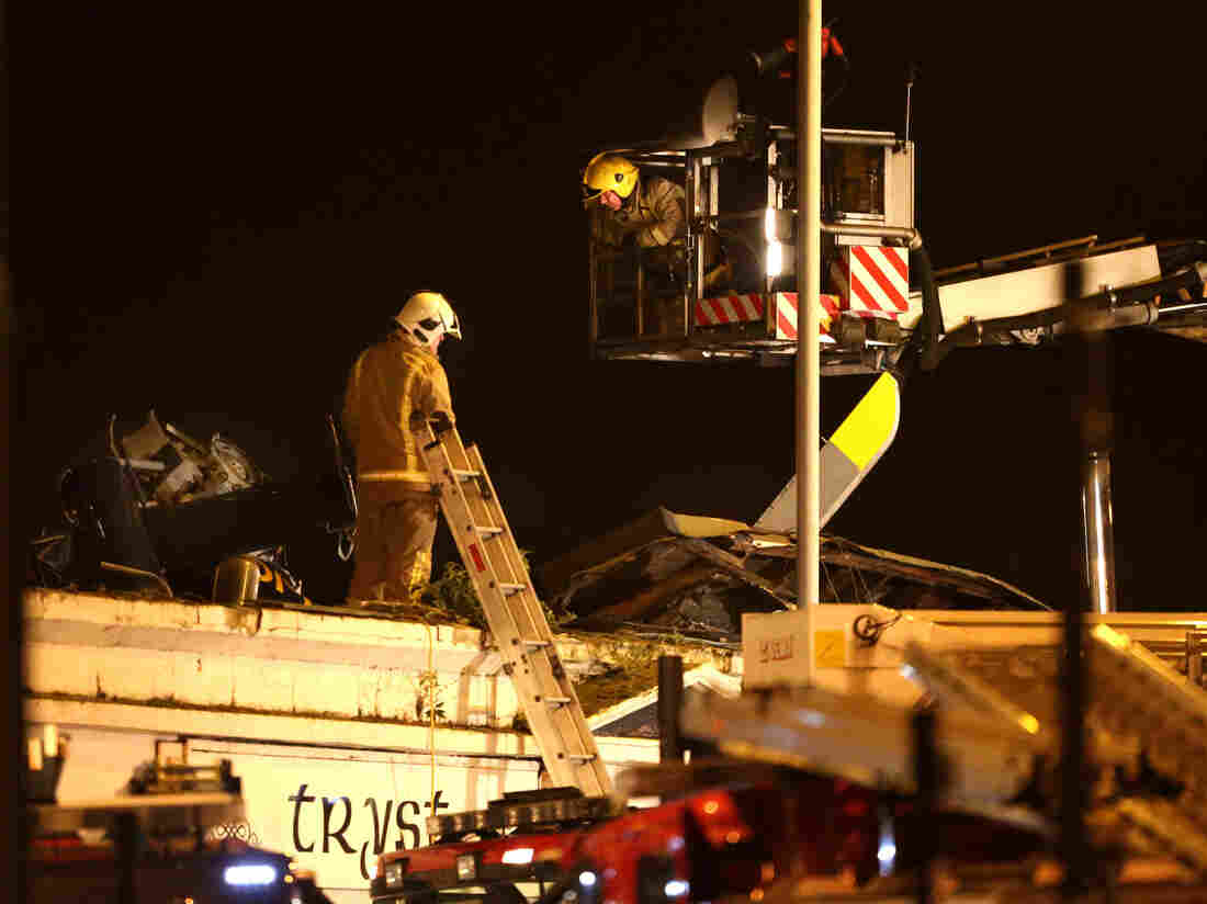 Firefighters work on the scene of a helicopter crash at The Clutha Bar in Glasgow, Scotland.