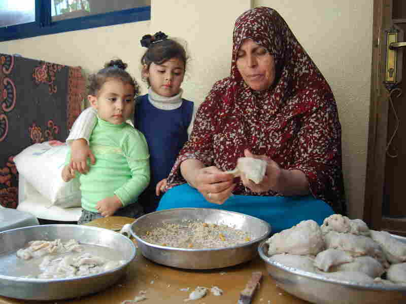 Palestinian refugee Lawahez Burghal stuffs tripe with rice and garbanzo beans for her family in their home in the Amari refugee camp in the West Bank. Many refugees still depend on the United Nations for food, health care and education.