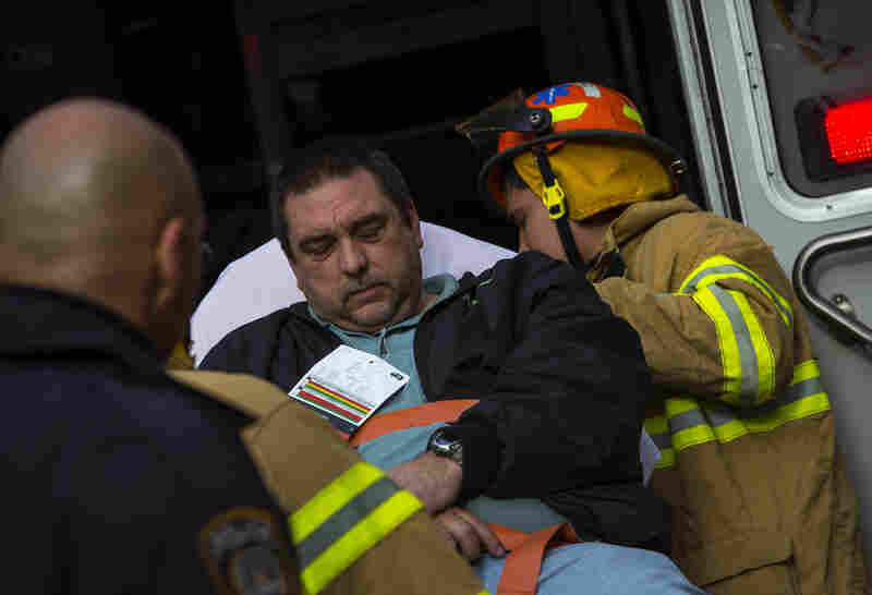 Emergency personnel evacuate a victim from the scene of the derailment.