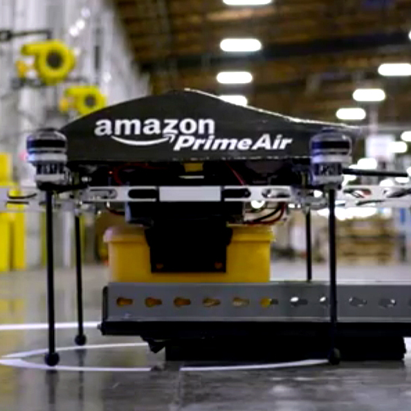 An Amazon drone spins its eight blades as it prepares to take off with a lunch-box-sized package, in a test run from one of the large retailer's warehouses.