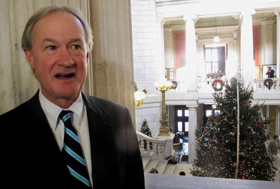 "Rhode Island Gov. Lincoln Chafee speaks with reporters in November of 2012, during the lighting the Statehouse Christmas tree. Chafee announced the ceremony 30 minutes ahead of time to avoid what he called the ""chaos"" of 2011's lighting, which was protested"
