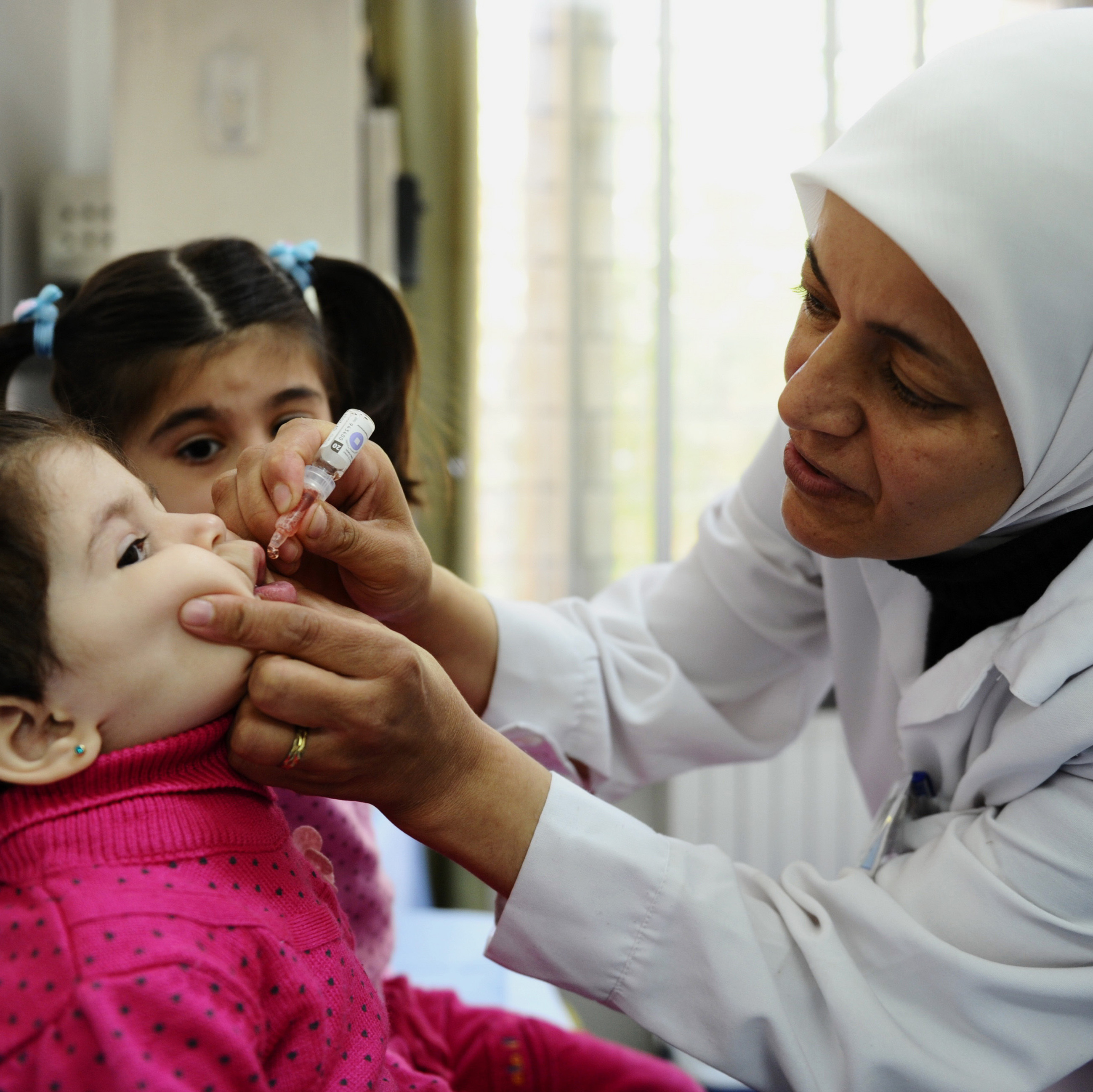 A health worker vaccinates a Syrian girl against polio at a clinic in Damascus on Oct. 29.