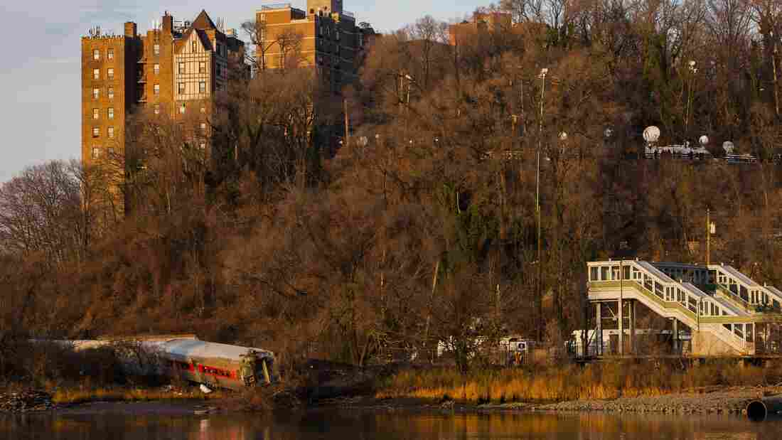 The wreckage of a Metro-North commuter train, which derailed Sunday just north of the Spuyten Duyvil station in Bronx, N.Y., lies on its side. The train was heading to Grand Central Terminal along the Hudson River.