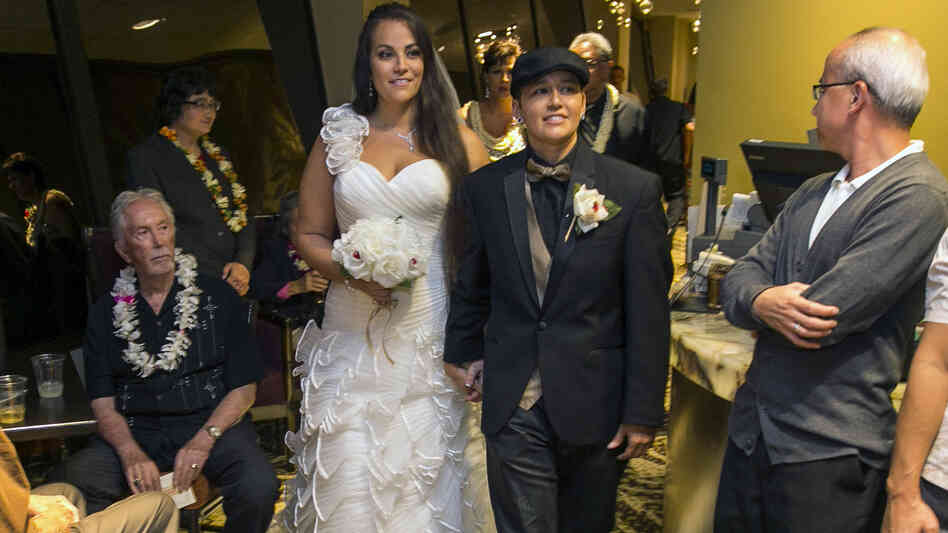 Saralyn Morales (center left) and Isajah Morales walk down the aisle at the Sheraton Waikiki in Honolulu shortly after Hawaii's new gay marriage