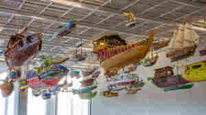 The boats of For Those in Peril on the Sea, by artist Hew Locke, hang in the entrance hall of the Perez Art Museum Miami, which opens this week.