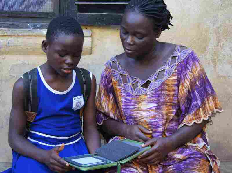 Deborah, a participant in Worldreader's iREAD project in Ghana, reads her favorite e-book with her mother. Worldreader has delivered more than 700,000 e-books via its e-reader programs.