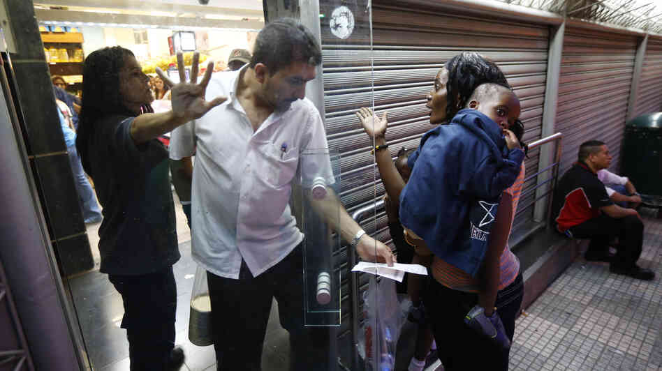 A woman and her child are barred from a supermarket that was closing its doors to ration milk products in Caracas on Nov. 15. Venezuela's President Nicolas Maduro, who was elected after the death of Hugo Chavez in March, is facing growing criticism over economic problems that include shortages of basic goods and inflation that's topped 50 percent this year.