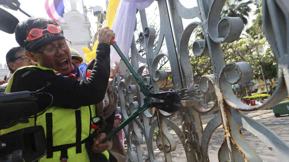 An anti-government protester cuts a lock on a gate outside Government