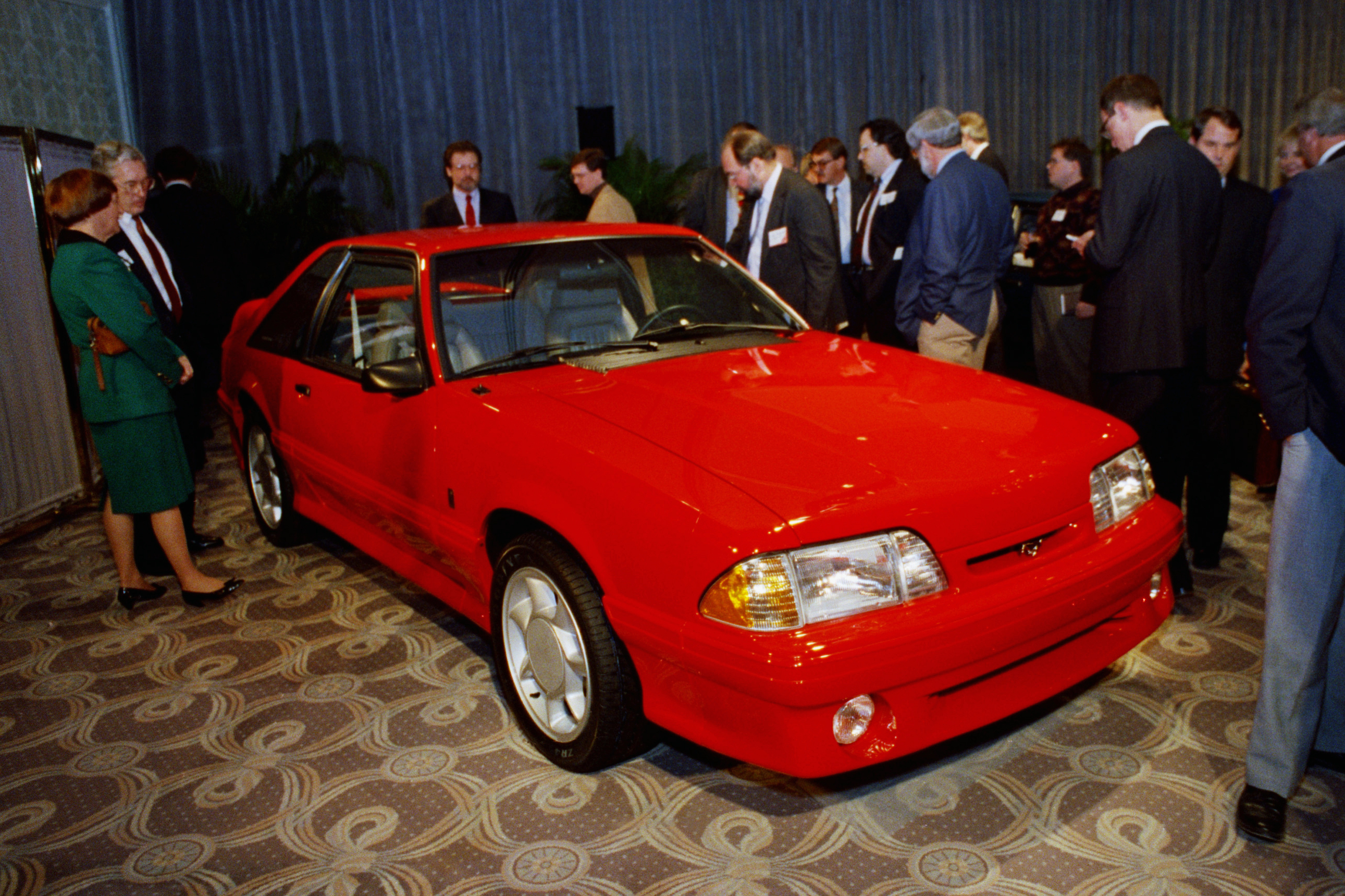 Reporters look over the limited edition 1993 Ford Mustang Cobra after its unveiling Feb. 6, 1992, in Chicago. This was part of the third generation of Mustangs that were produced from 1979 to 1993.