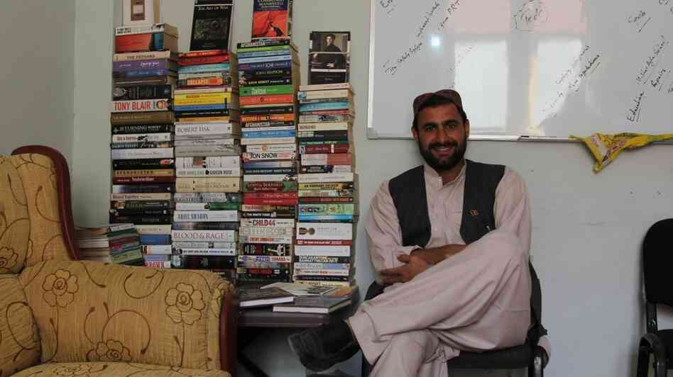 Auliya Atrafi in his office in Nad Ali, next to a selection of the books he had shipped from England. His library is one of his prized possessions, and he shipped them because he's unlikely to find these books in his native Afghanistan.