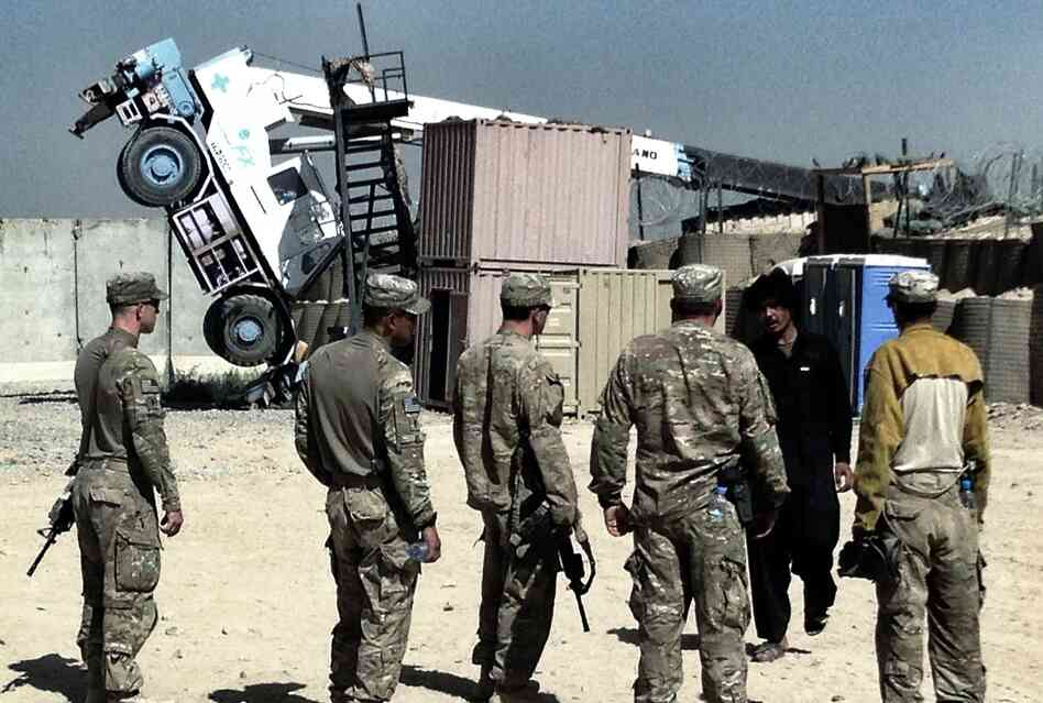 U.S. soldiers look at a crane that tipped over while trying to move a CHU, or Containerized Housing Unit, at a small COP, or Combat Outpost, in southern Afghanistan. A dozen years of war in Iraq and Afghanistan have created a whole new military vocabulary.