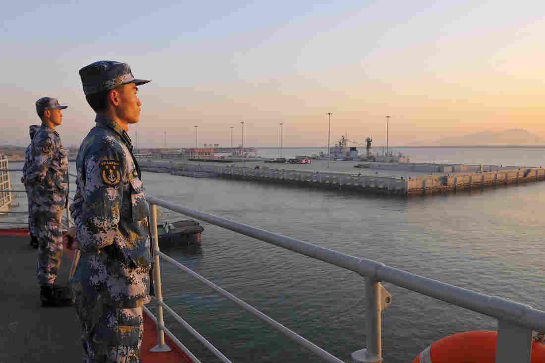 Chinese naval soldiers stand guard on China's first aircraft carrier Liaoning as it travels toward a military base in Sanya, Hainan province, in this undated picture made available on Nov. 30.