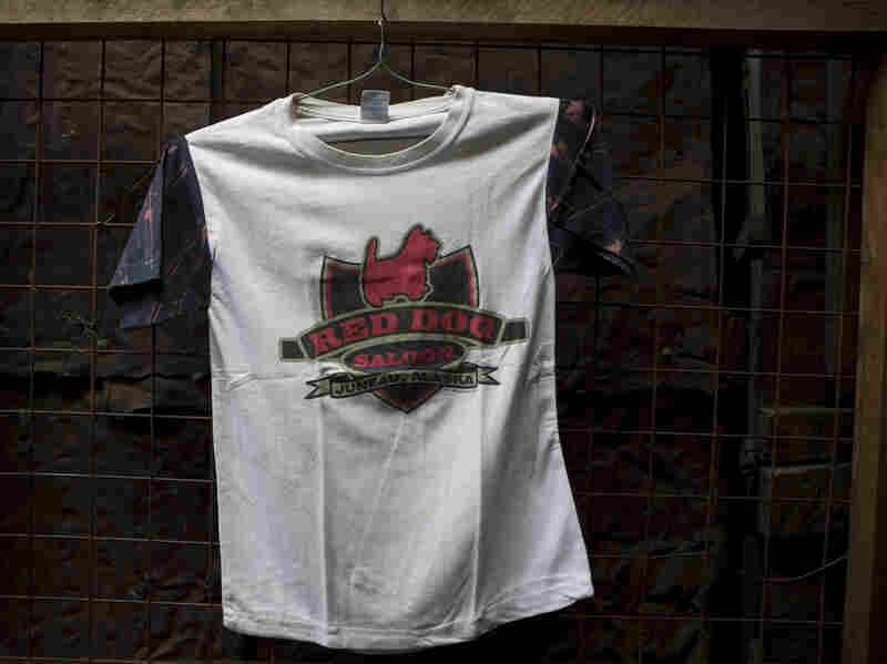"A T-shirt for sale at Gikombo Market in Nairobi, Kenya. The shirt reads ""Red Dog Saloon - Juneau, Alaska."""