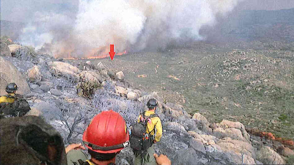 A photo taken by the Granite Mountain Hotshots on June 30 shows their position on a ridge, with a red arrow indicating the original location