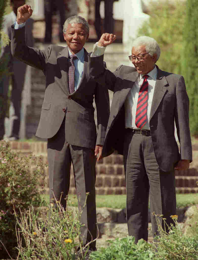 Nelson Mandela and Walter Sisulu raise their fists in 1990, one day after Mandela was released from jail.