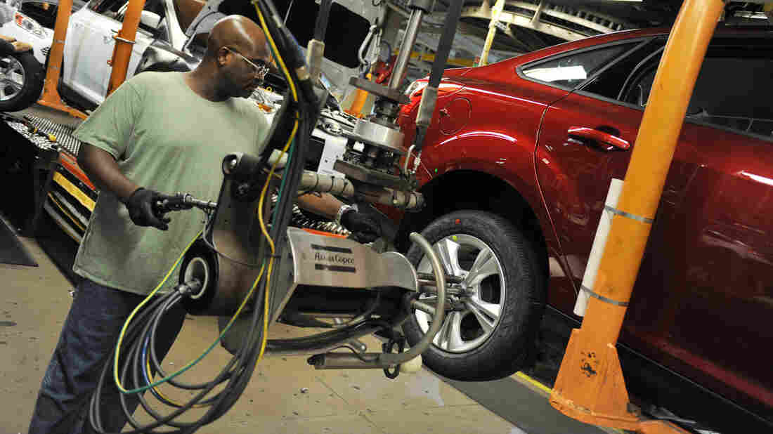 An auto worker tightens bolts on the wheel of a Focus at a Ford plant in Wayne, Mich. Re