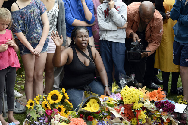 A woman prays outside the house of former South African President Nelson Mandela in Johannesburg on Friday, the day after his death.