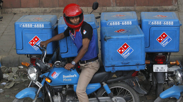An employee rides a motorcycle to deliver Domino's pizzas i