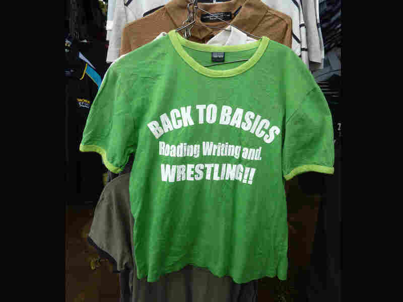 "A T-shirt for sale in an outdoor market in Kisumu, Kenya. The shirt reads ""BACK TO BASICS. Reading Writing and, WRESTLING!!"""