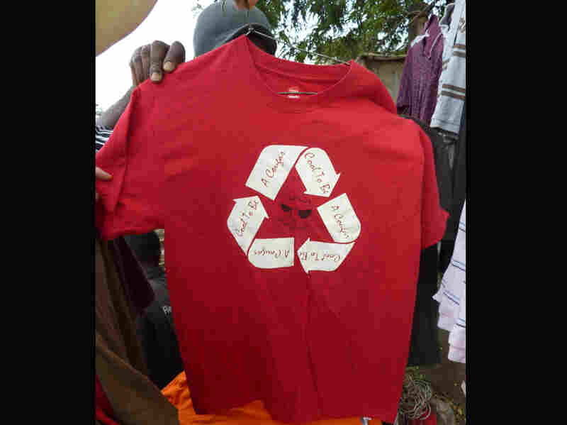 "A T-shirt for sale in an outdoor market in Kisumu, Kenya. The shirt reads ""Cool To Be A Cougar, Cool To Be A Cougar, Cool To Be A Cougar."""