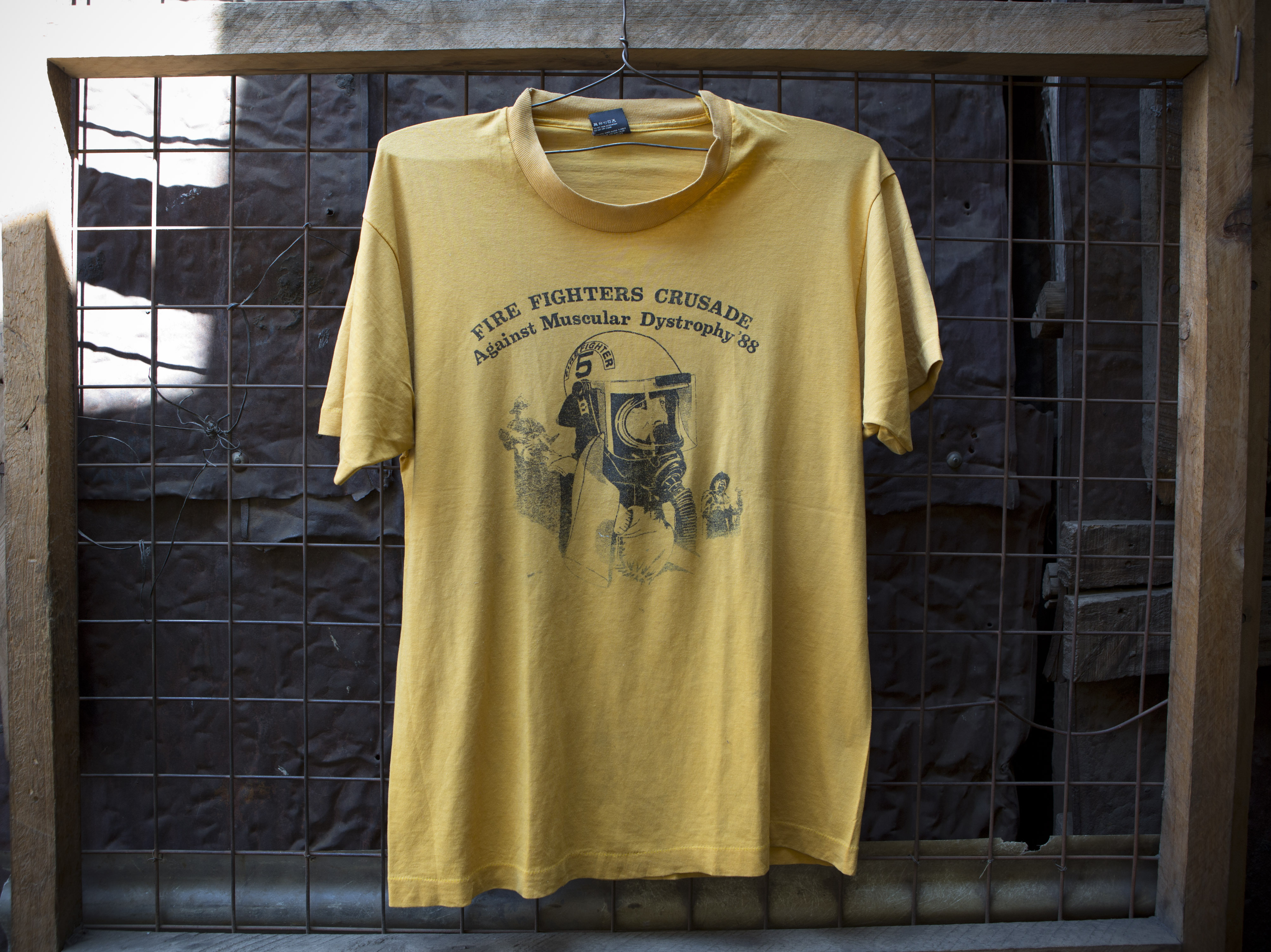 "A T-shirt for sale at Gikombo Market in Nairobi, Kenya. The shirt reads ""Fire Fighters Crusade Against Muscular Dystrophy '88."""