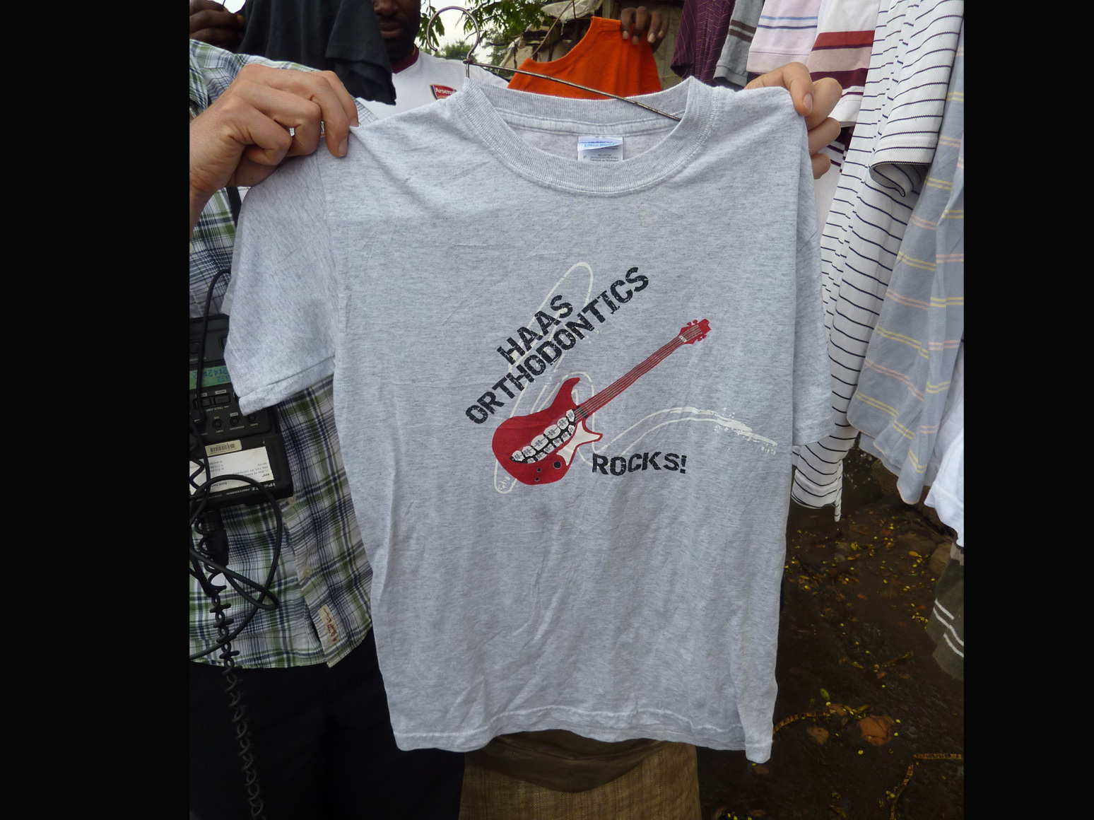 "A T-shirt for sale at an outdoor market in Kisumu, Kenya. The shirt reads ""Haas Orthodontics Rocks!"""