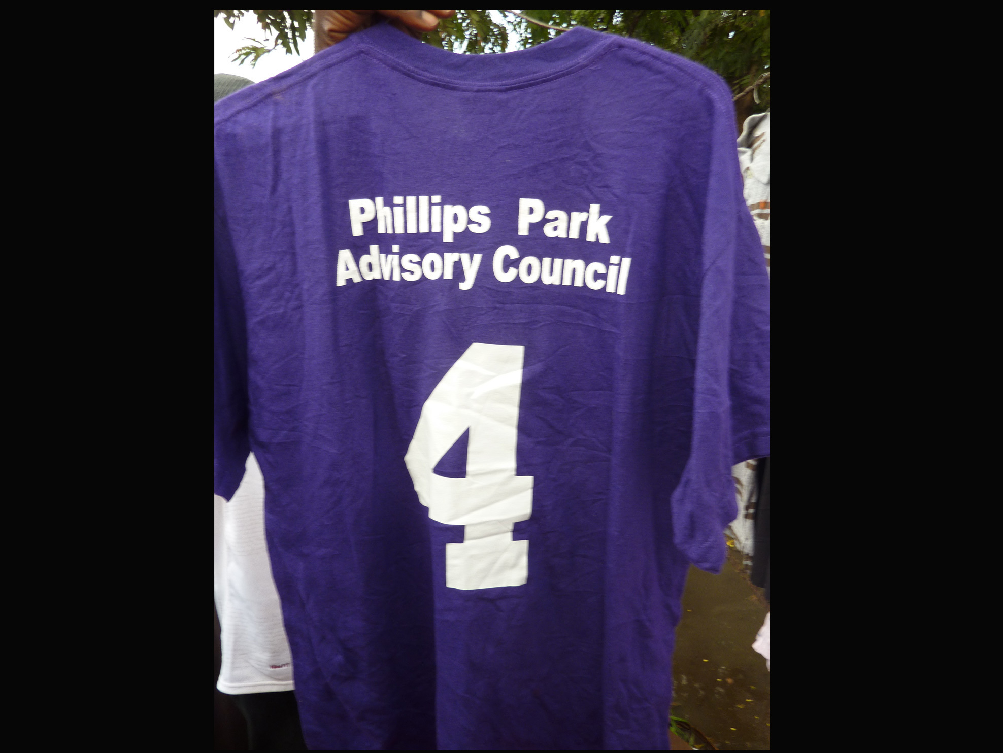 "A T-shirt for sale at an outdoor market in Kisumu, Kenya. The shirt reads ""Phillips Park Advisory Council."""