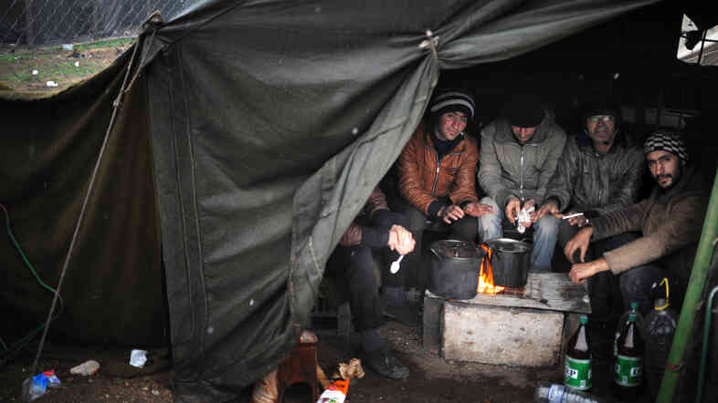 Refugees warm their hands at a refugee camp in Harmanli, Bulgaria, on Nov. 27. More Syrians are turning u