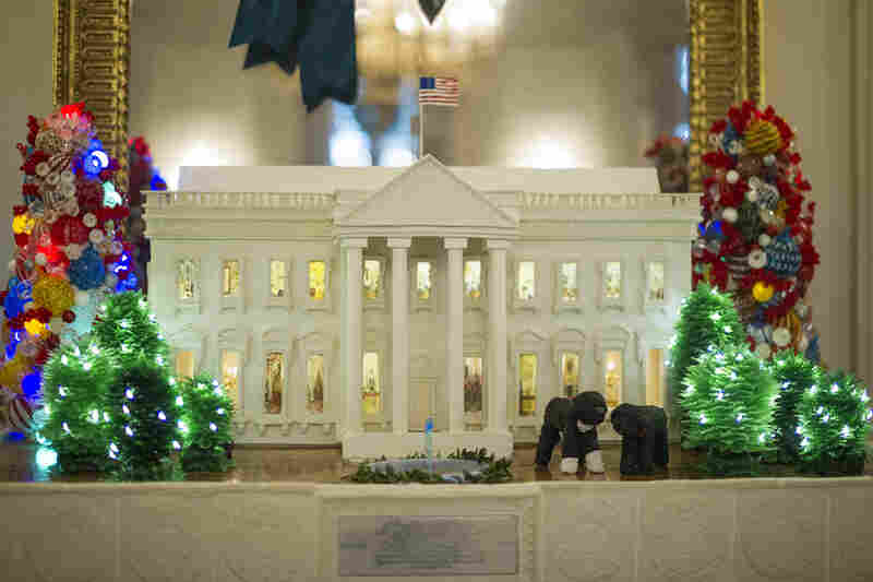 A 300-pound gingerbread White House is the centerpiece at a table in the State Dining Room.