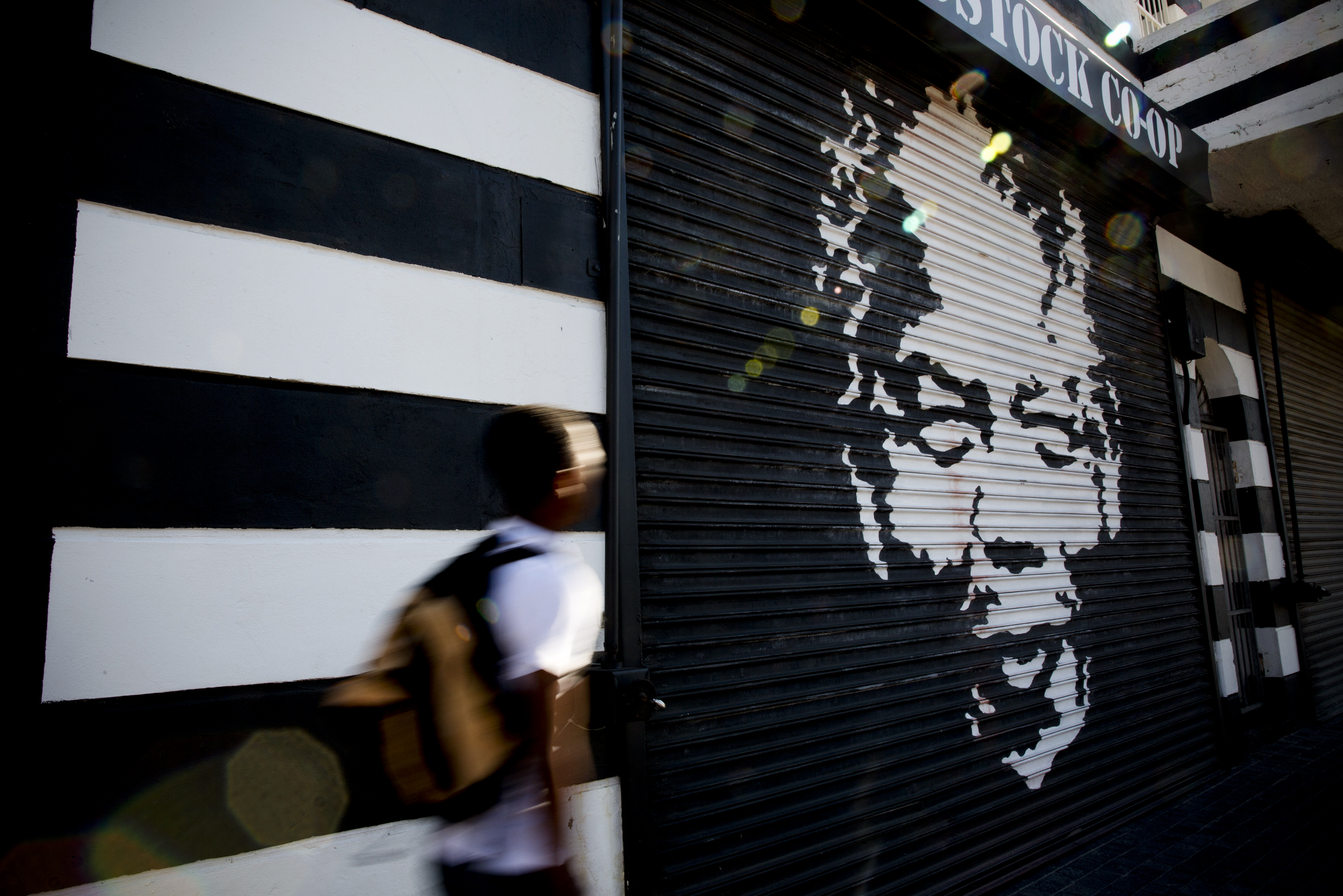 A man walks past a mural of Mandela in Woodstock, a Cape Town suburb. Mandela's portrait is no stranger to the walls of Cape Town.