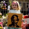 Karla Truter, aged 3, holds up a portrait of Mandela outside the City Hall.