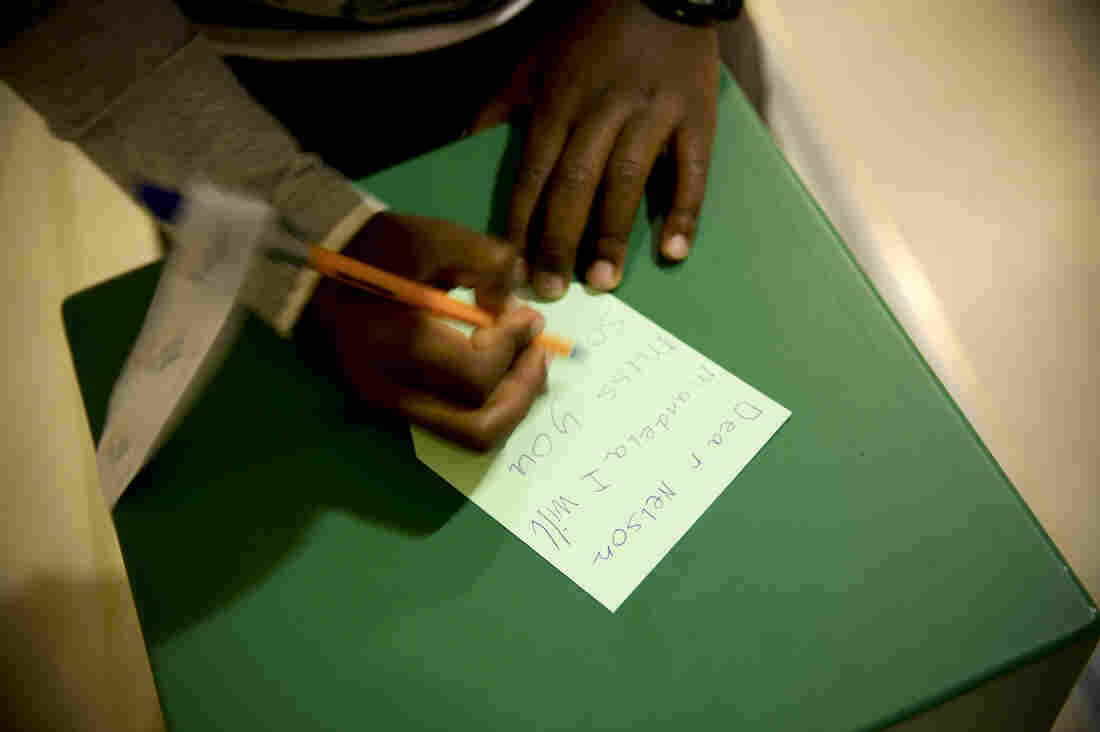 A young boy writes a goodbye message to Mandela at Cape Town's Civic Center Nelson Mandela exhibition. The exhibition opened earlier this year in celebration of Mandela's 95th birthday.