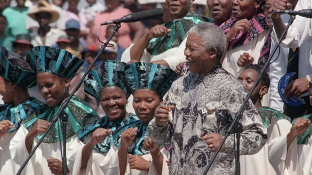 South African President Nelson Mandela joins the choral group at the signing of the country's new constitution at Sharpeville stadium in 1996.  Mandela lived a life filled with rich musical associations. (AFP/Getty Images)