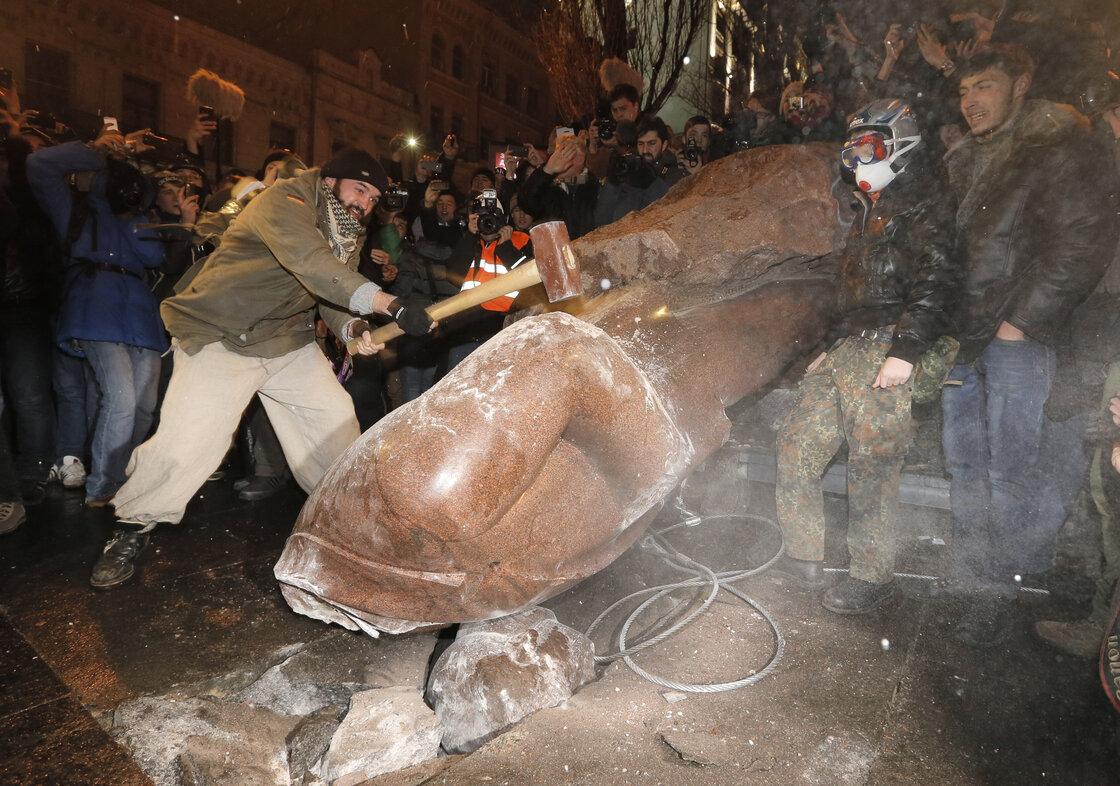 Ukrainians break a monument of Vladimir Lenin in center Kiev, Ukraine, on Sunday.