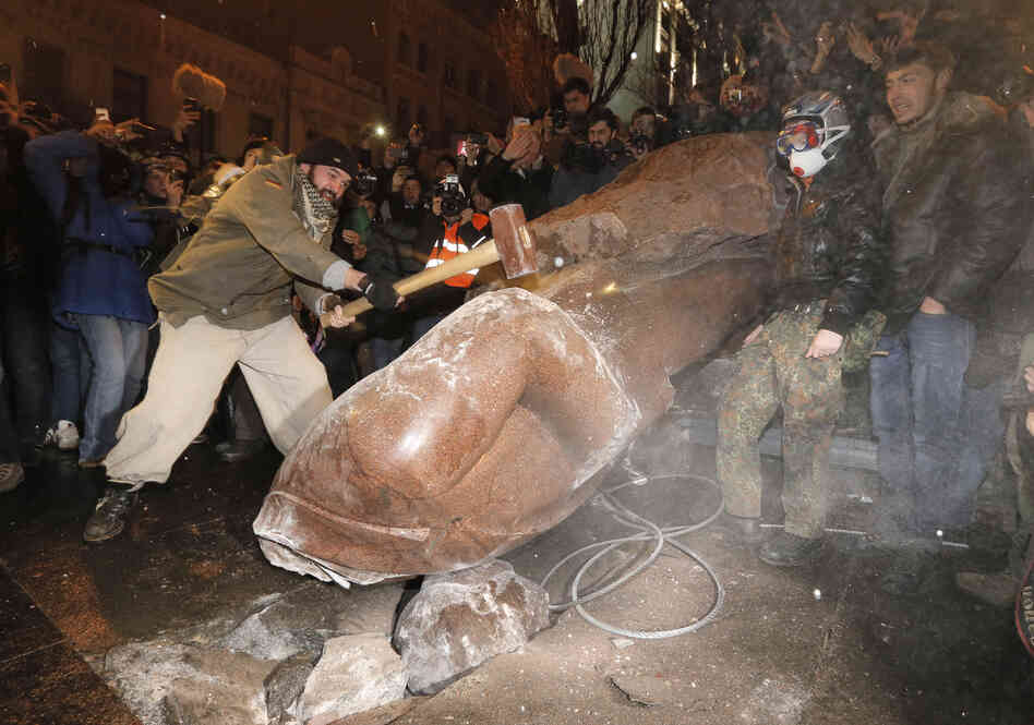 Ukrainians break a monument of Vladimir Lenin in center Kiev, Ukraine, on Sunday.