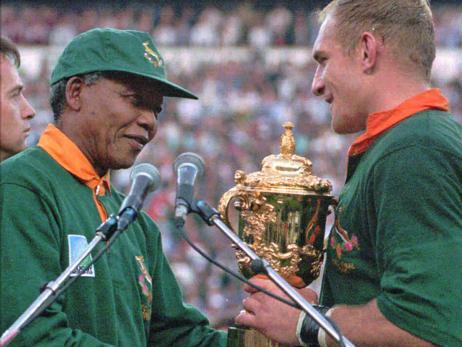 In 1995, South African rugby captain Francios Pienaar  receives the Rugby World Cup from President Nelson Mandela, who wears the green Springbok jersey.