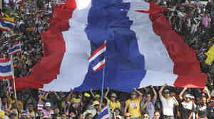 Anti-government protesters carry a Thai national flag as they march Monday in Bangkok.