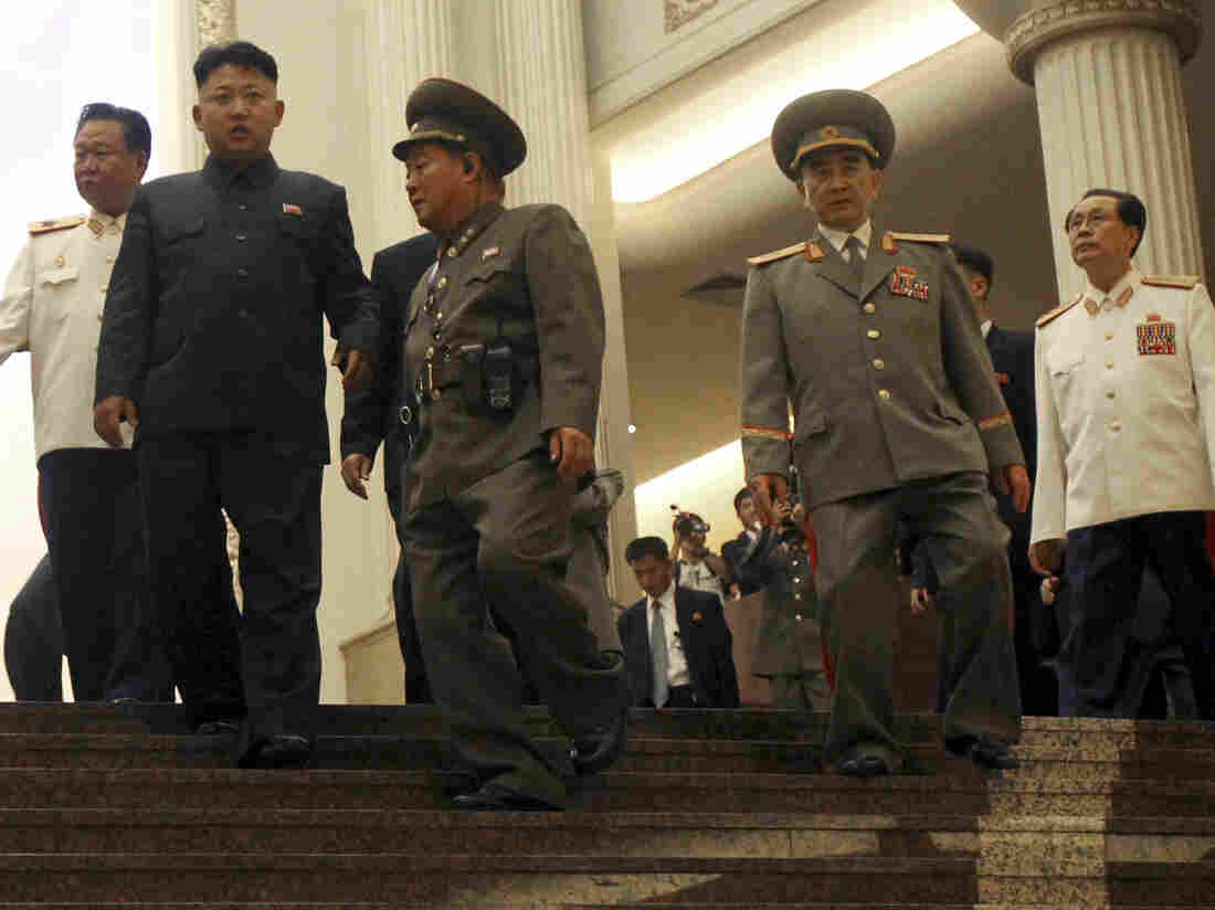 In July, North Korean leader Kim Jong Un (second left) is flanked by top advisers, including his uncle Jang Song Thaek, at far right in white uniform.