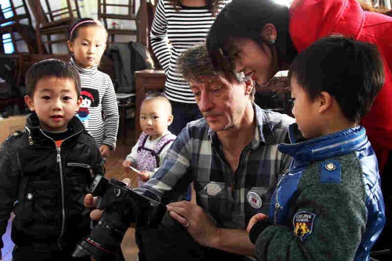 Lutz Michaelis, a robotics engineer from Germany, shows a Chinese family a preview of their free portrait last weekend in Shanghai.